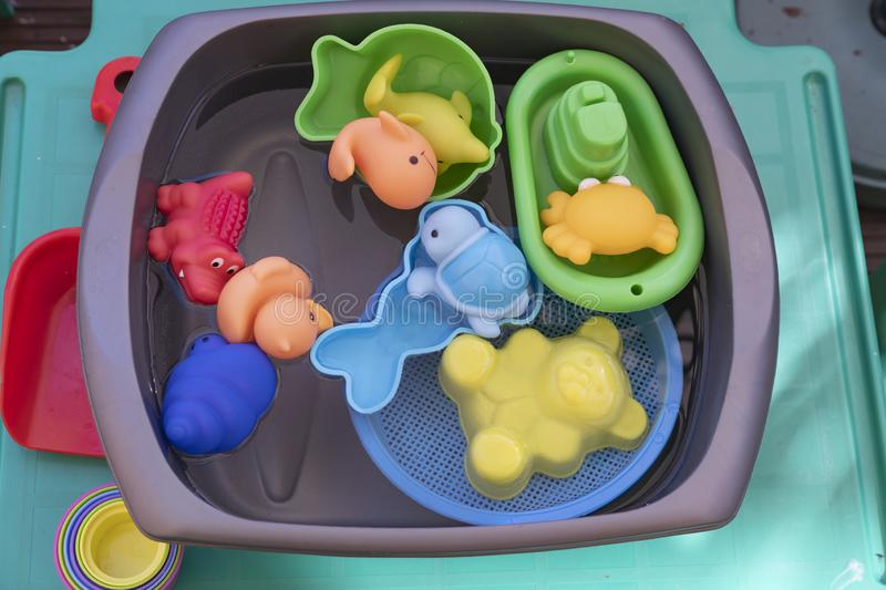 Childrens water play toys in bright colours. Bowl of water containing water and water toys for a child to have cool fun stock image