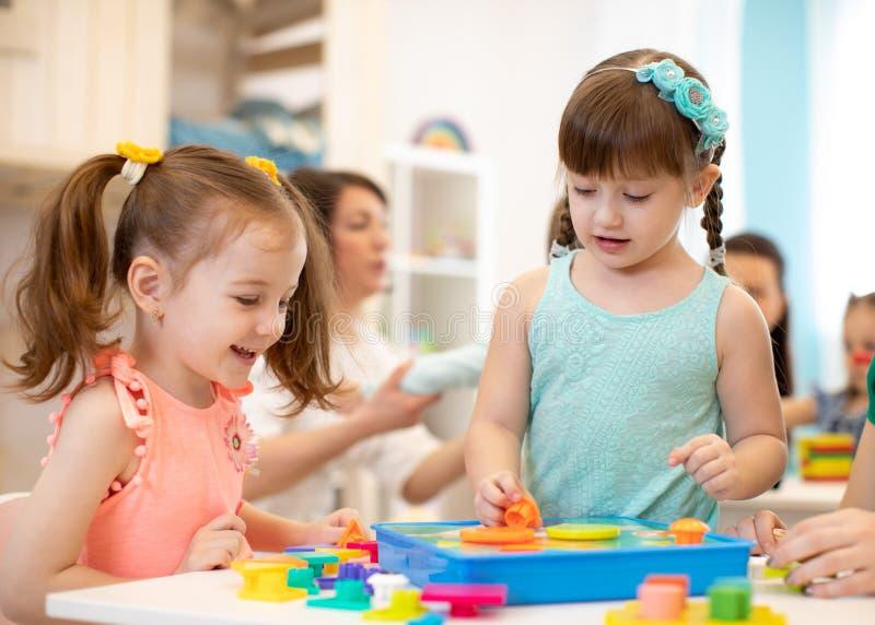 Childs играя с отработочными игрушками на таблице в детском саде стоковые изображения rf