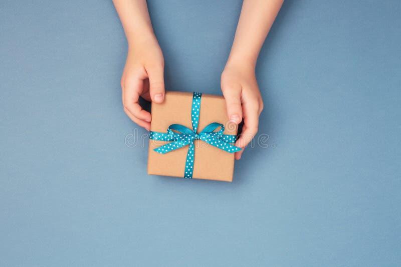 Childs übergibt das Halten von einer Geschenkbox eingewickelt im Kraftpapier stockbilder