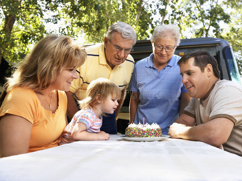Childs birthday celebration. Three generation Caucasian family seated at picnic table celebrating female childs birthday with cake royalty free stock photography