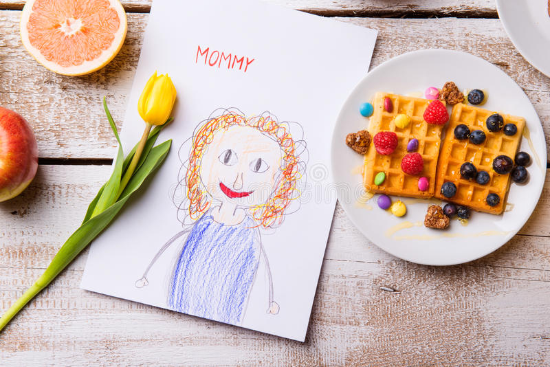 Childs drawing of her mother, yellow tulip, waffles royalty free stock photo