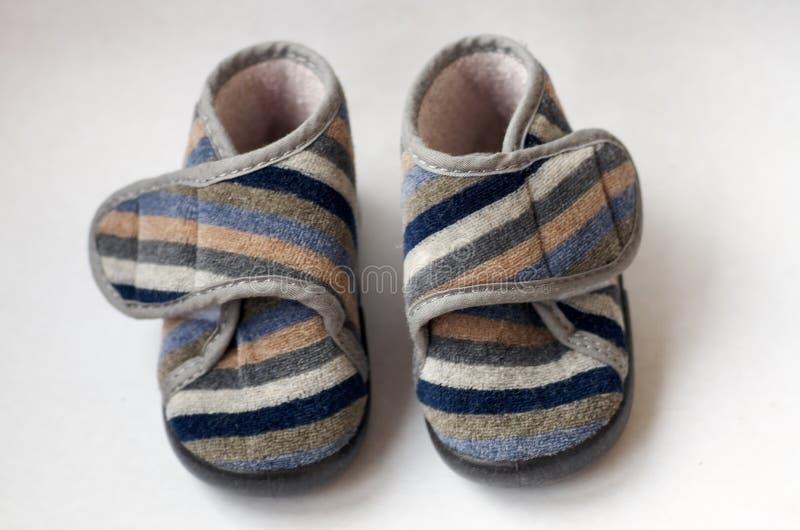 Childs färgade skor på en vit bakgrund royaltyfria foton