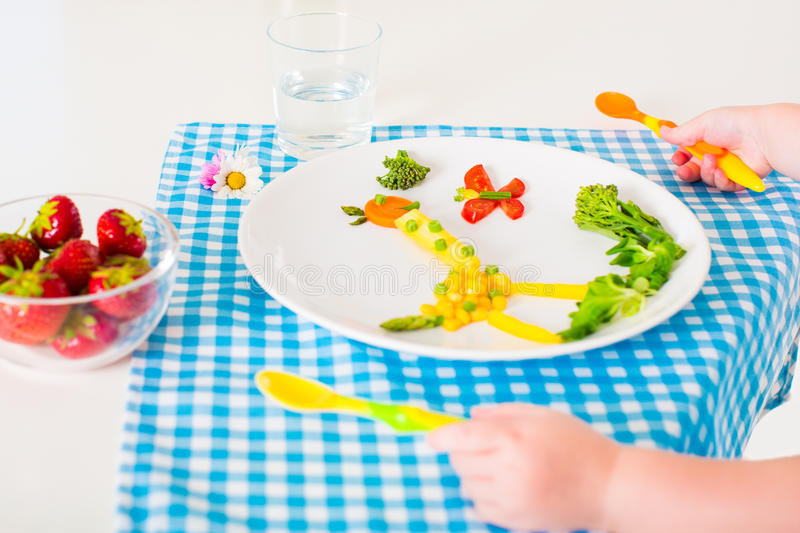Childs hand and healthy vegetable lunch for kids l. Healthy vegetarian lunch for kids little , vegetables and fruit served as animals, corn, broccoli, carrots royalty free stock images