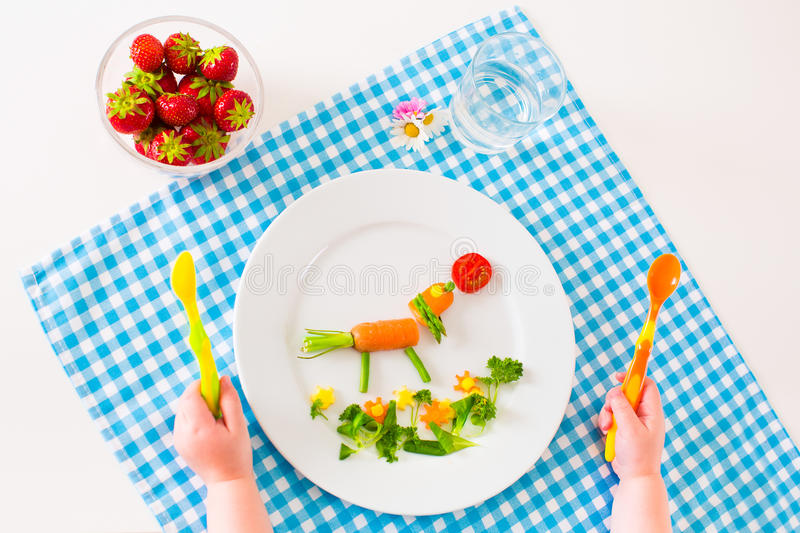 Childs hand and healthy vegetable lunch. Healthy vegetarian lunch for little kids, vegetables and fruit served as animals, corn, broccoli, carrots and fresh stock photo
