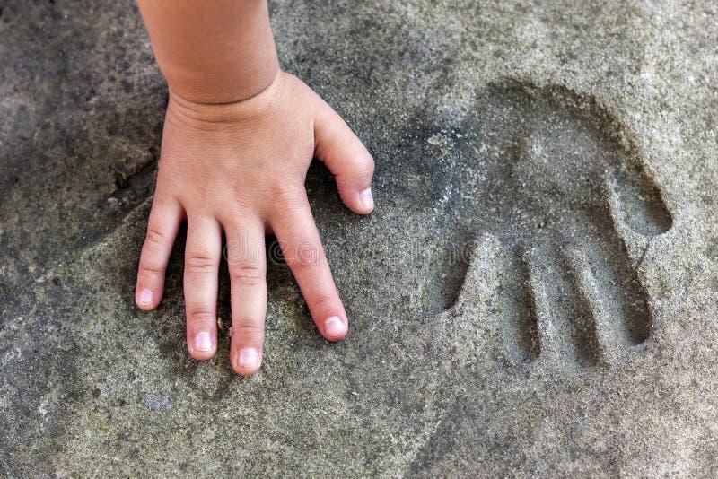 Childs hand och minnesvärd handprint i betong royaltyfria foton