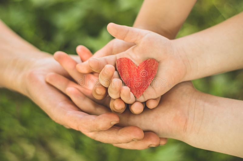 Childs hand and old hand grandmother hold heart. Concept idea of love family protecting children and elderly people grandmother. Friendship togetherness stock photo