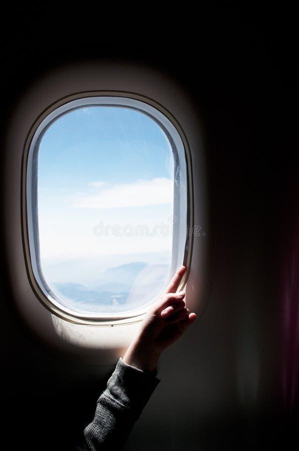 Childs hand på ett flygplanfönster royaltyfri bild