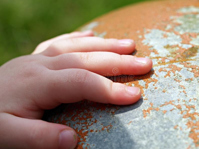 Childs hand på rostig yttersida royaltyfri foto