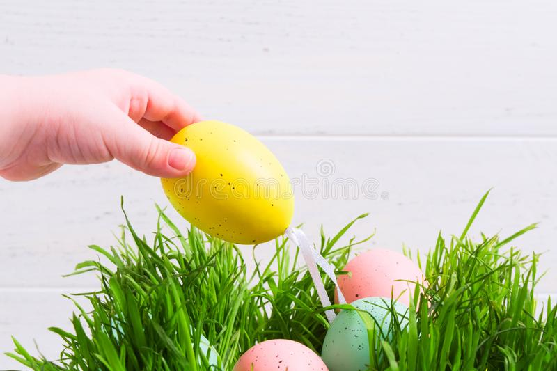 Childs hand take yellow Easter egg from grass. Easter hunt concept stock photo