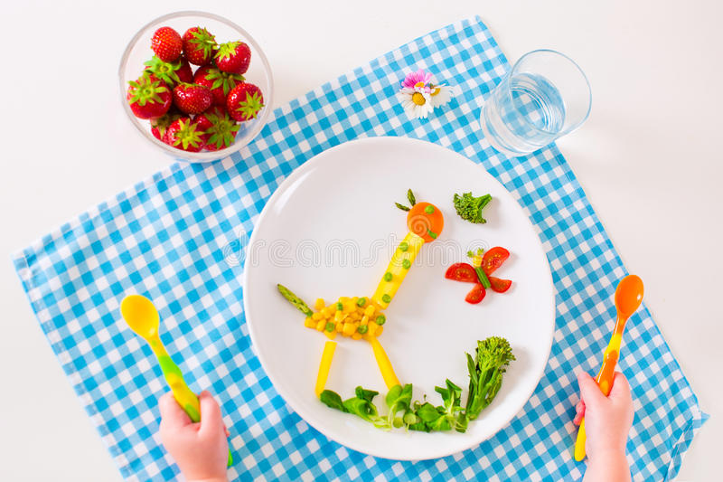 Childs little hand and healthy vegetable lunch. Healthy vegetarian lunch for little kids, vegetables and fruit served as animals, corn, broccoli, carrots and stock photos