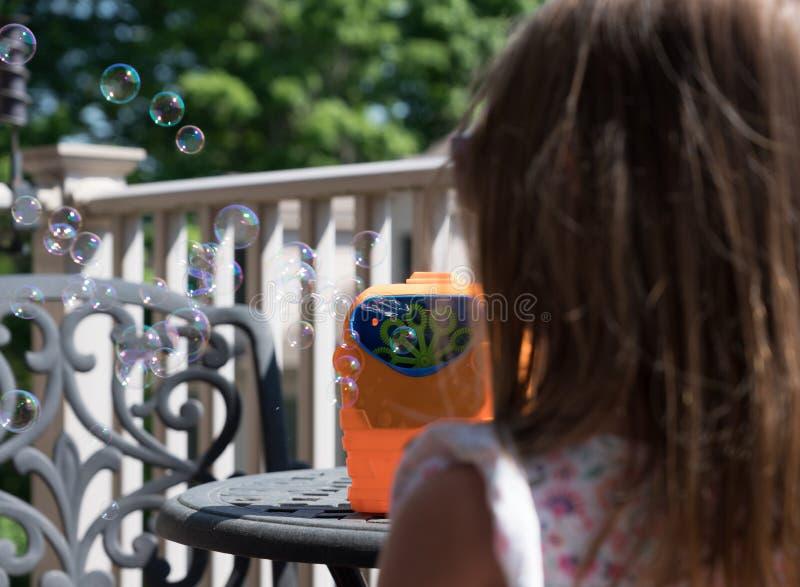 Childs mekanisk såpbubblatillverkare eller blåsare med flickan framme arkivfoto