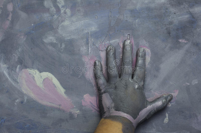 Childs painted hand over a painted wood surface. Grey and heart royalty free stock photo