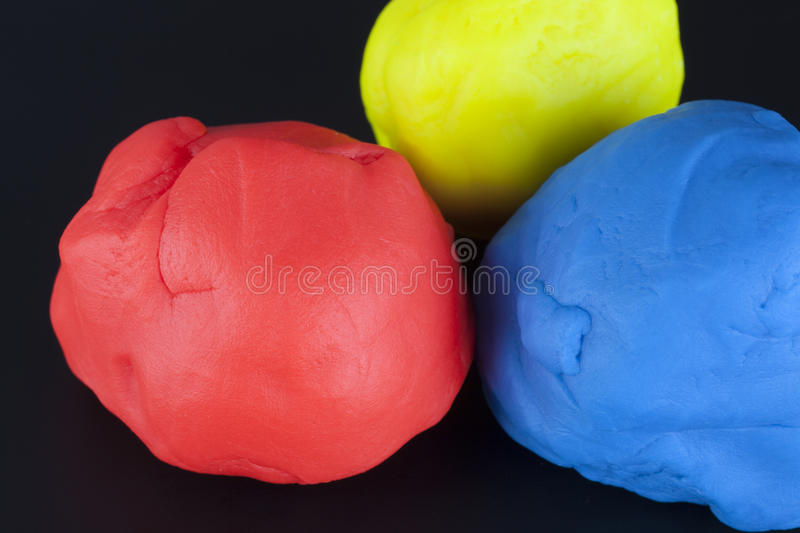 Childs play clay. Colorful child's play clay (Red, Yellow, Blue) on black background stock photo
