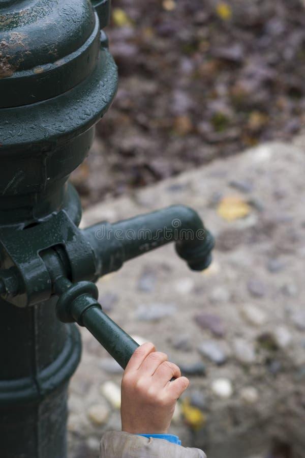 Childs ręka na uchwycie ulicznej pompy wodnej obrazy royalty free