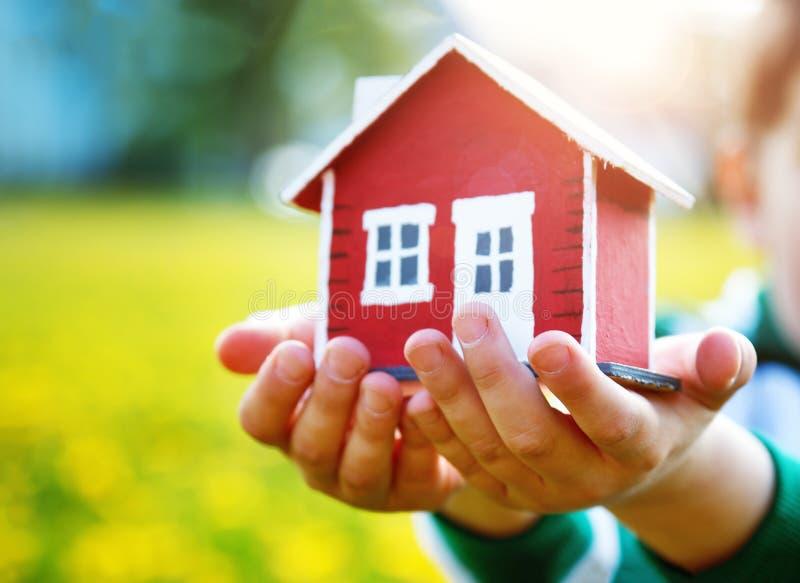Childs ręki trzyma czerwień modela dom fotografia royalty free