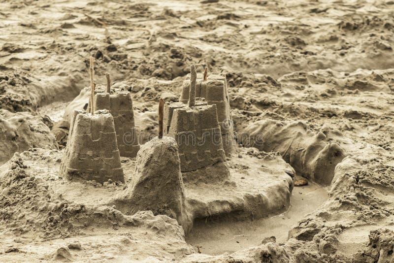 Childs sandslott som överst göras från former med pinnar för flaggor och en övergiven vallgrav på stranden - selektiv fokus arkivfoto