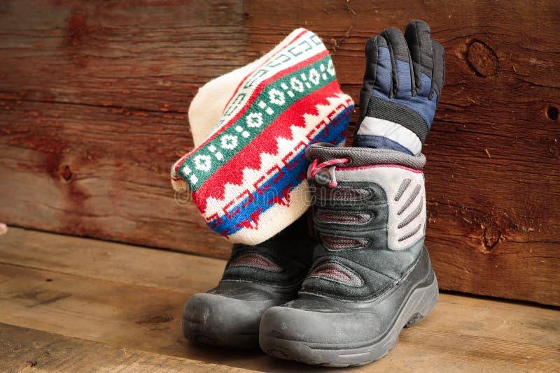 Childs snökängor med ett vinterlock och handskar arkivfoton