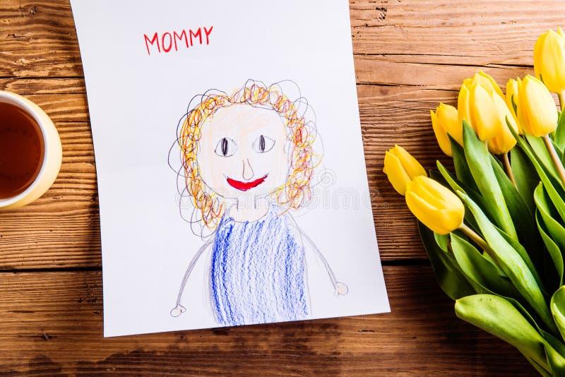 Childs-Zeichnung ihrer Mutter, gelbe Tulpen, Teeschale stockfotos