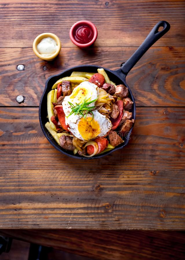 CHILEAN FOOD. CHORRILLANA - french fries topped with beef sliced, tipical sausages chorrisos, fried onion and eggs stock image