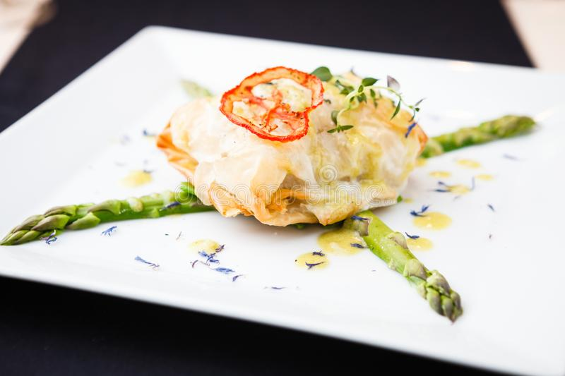 Chilean sea-bass. In papilliote on a plate stock image