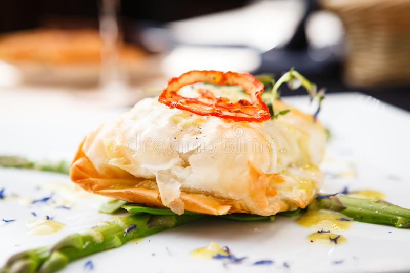Chilean sea-bass. In papilliote on a plate stock photography