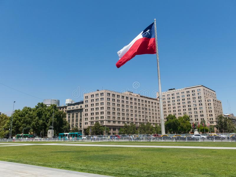 Chileans walking near the giant flag on Avenida La Alameda with the citizenship Square, in downtown Santiago de Chile. Chile royalty free stock images
