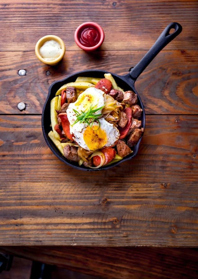 Chileens voedsel CHORRILLANA - frieten met gesneden rundvlees, tipical worstenchorrisos, gebraden ui en eieren worden bedekt dat stock afbeelding