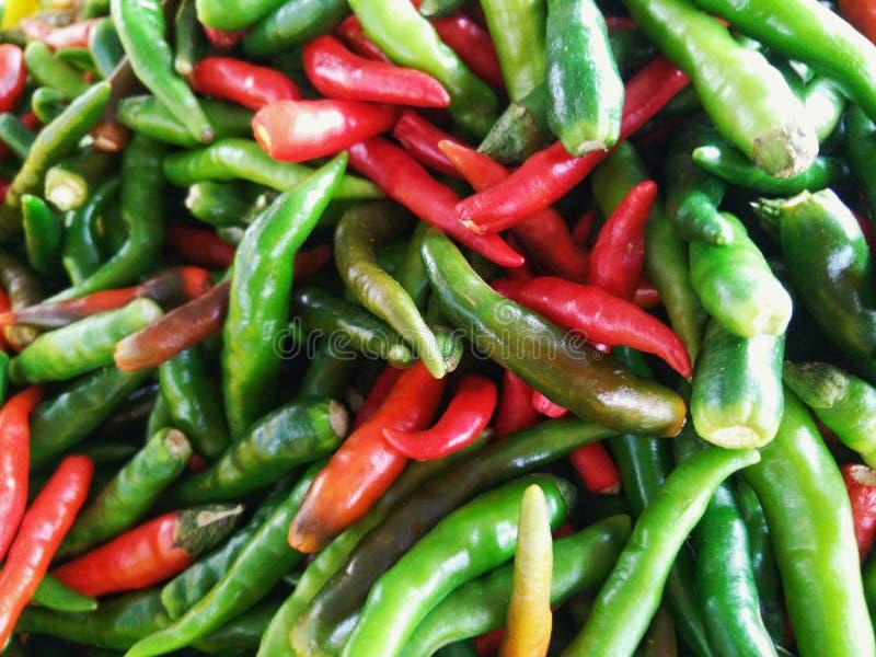 Chiles picantes rojos y verdes en el mercado imagen de archivo