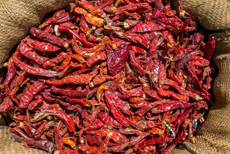 Chiles secos rojos en bolso de la lona fotos de archivo