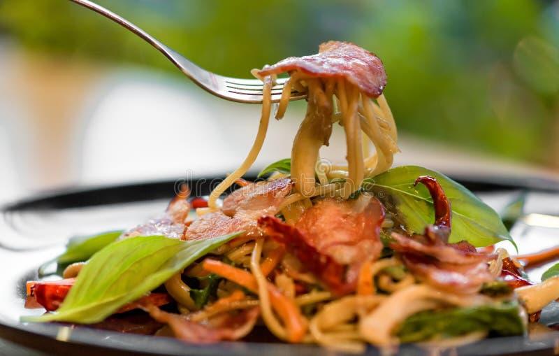 chiles y salsa secados espaguetis picantes deliciosos de la albahaca con el tocino y la seta, cierre hermoso encima del tocino pi fotografía de archivo