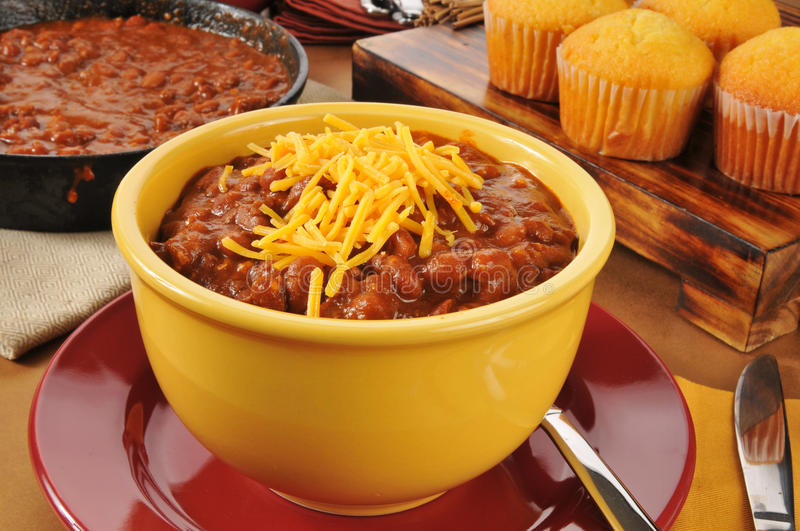 Chili con carne with cornbread muffins. A bowl of chili con carne with cheddar cheese and cornbread muffins royalty free stock photo