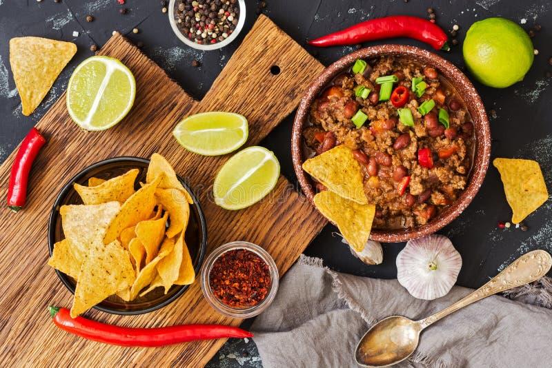 Chili con carne Het Mexicaanse Spaanse pepervoedsel met vlees en graan breekt nachos op een rustieke achtergrond af Mening van hi stock afbeeldingen