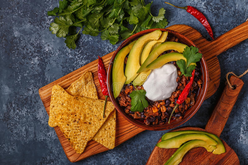 Chili con carne i bunke med avokadot och gräddfil royaltyfria foton