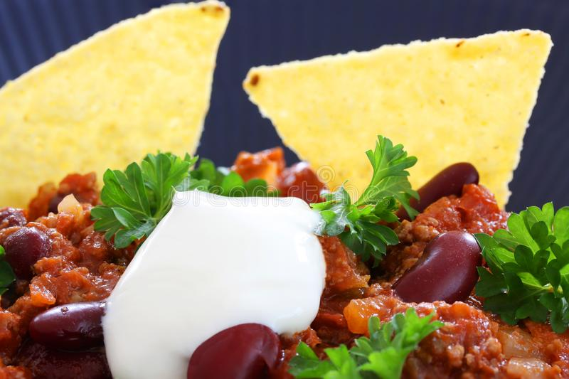 Chili con carne meal in a rustic bowl. Traditional dish of mexican cuisine with kidney beans, minced meat, parsley, tortilla chips royalty free stock images