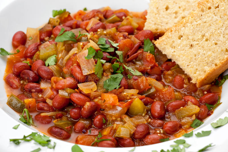Chili with Cornbread. Close up of vegetarian chili with beans, and cornbread in a white bowl stock photo