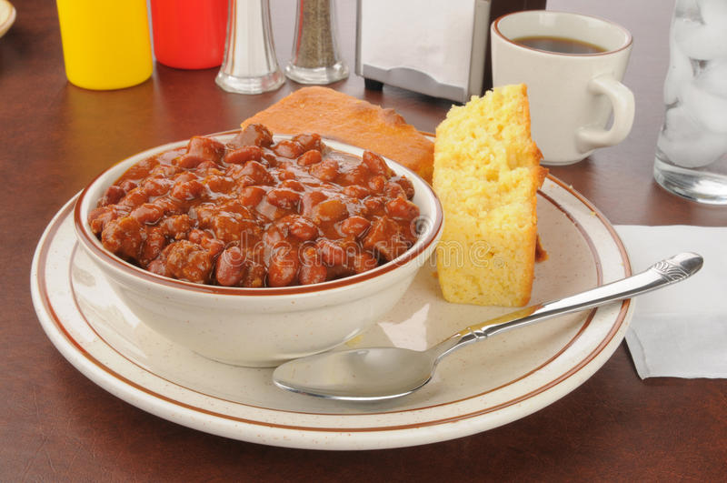 Chili with cornbread. A bowl of chili with sliced cornbread stock image