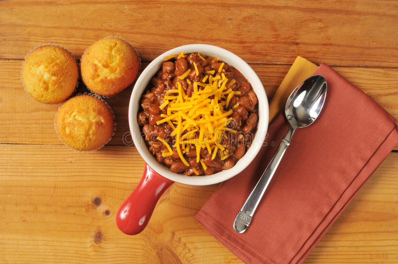 Chili and cornbread. A bowl of chili and cornbread from a high angle view on a rustic wooden table royalty free stock photos