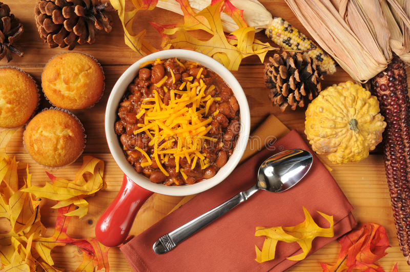 Chili and cornbread muffins. A stoneware crock of chili con carne with cornbread muffins and cheddar cheese royalty free stock image