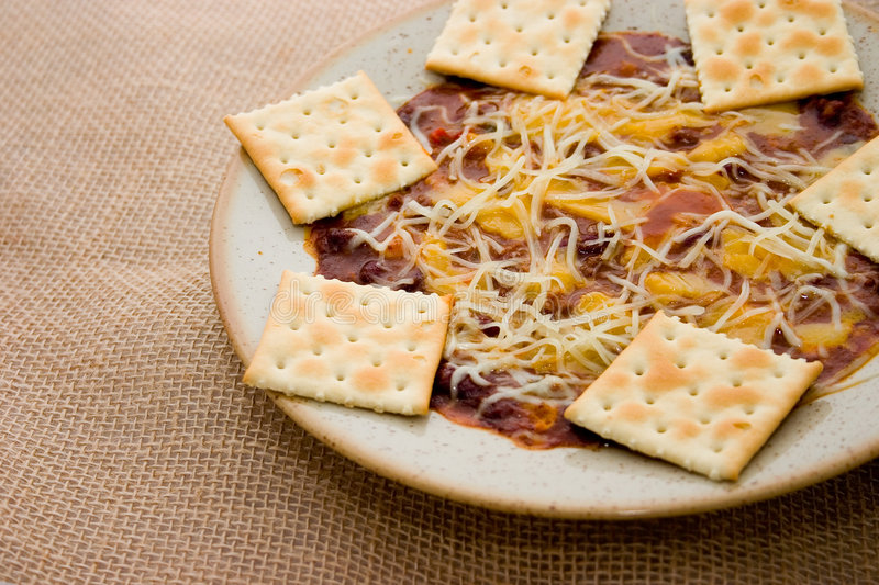 Chili and crackers. Stoneware bowl filled with chili topped with melted cheese and crackers royalty free stock photos