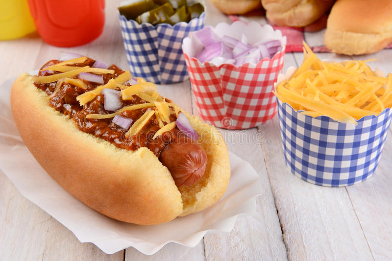Chili Dog and Condiments. Closeup of a grilled chili dog with cheese and onions on a rustic wood picnic table. More buns and condiments fill the background stock photo