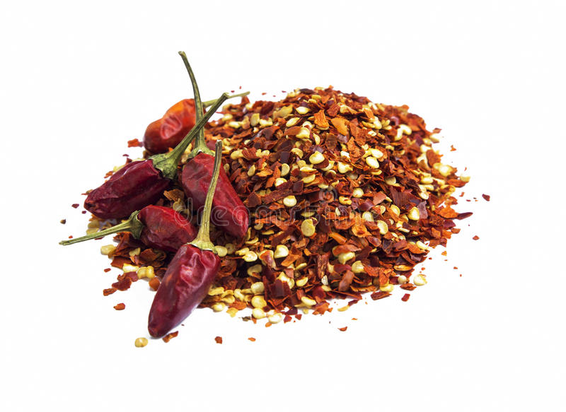 Chili flakes and peppers isolated. Chili flakes and peppers heap isolated on white stock photography