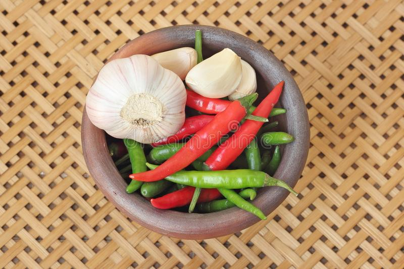 Chili and garlic in mortar on wooden textured. Basket weaving background royalty free stock photography