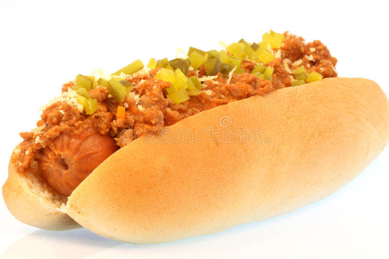 Chili hot dog. Hot dog against white background with chili , onions and pickles on top royalty free stock image