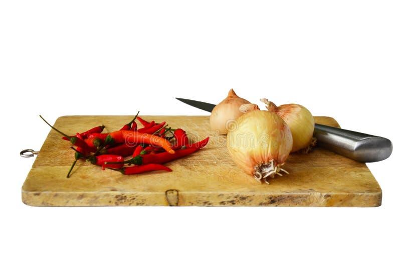 Chili i cebula z kuchni narzędziami na białym tle obraz royalty free