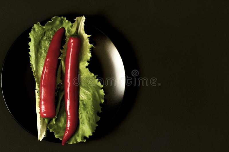 Chili pepper with greens on a plate on a black background. Top view royalty free stock photography