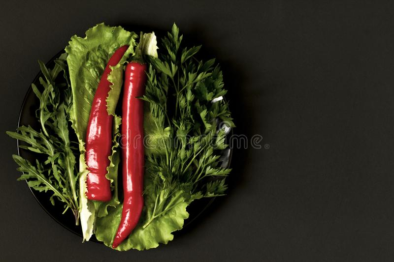 Chili pepper with greens on a plate on a black background. Top view royalty free stock photos