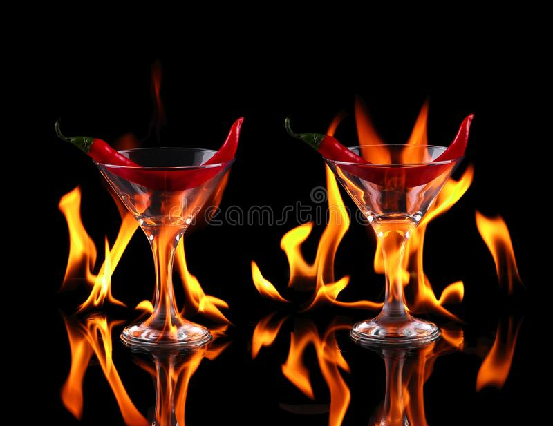 chili pepper in a martini glass with a fire on a black backg stock photo