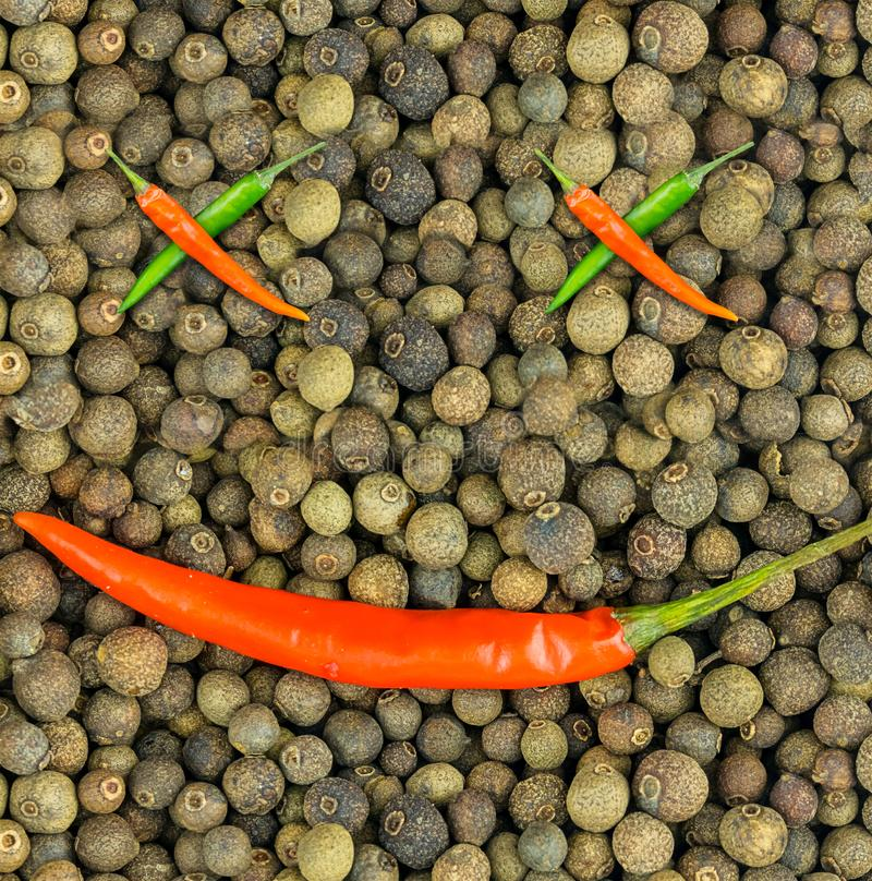 Chili pepper ornament foundation on a background of black pepper folded diagonal pods crosses eyes and mouth joyful face stock photo