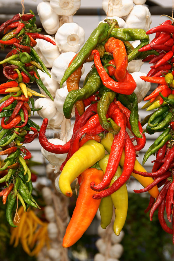Chili peppers ang garlic. Colorful chili peppers ang garlic on sale at a market stall royalty free stock photos