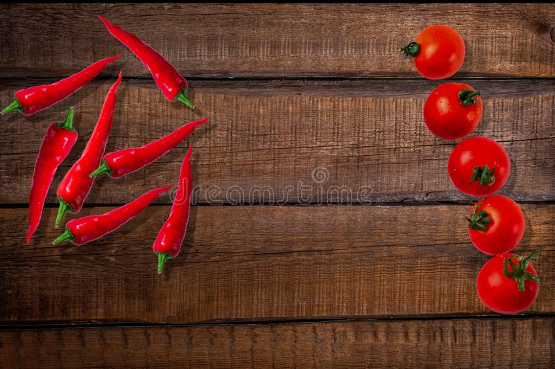 Chili peppers and cherry tomatoes on a wooden background. Fresh cherry tomatoes and hot chilli peppers laid out on a wooden table. spicy foods stock images